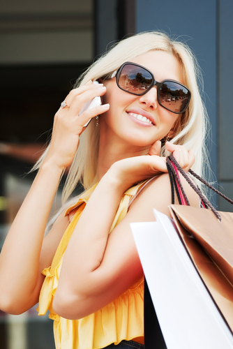 Beautiful young woman holding shopping bags in one hand and talking on a cell phone