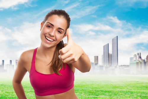 A happy girl in a pink sports bra giving a thumbs up on a grassy, city, and sky background