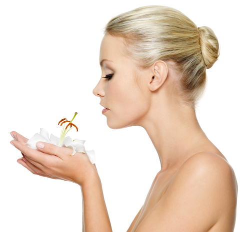 A sideview of a woman smelling a flower in her hands on a white background