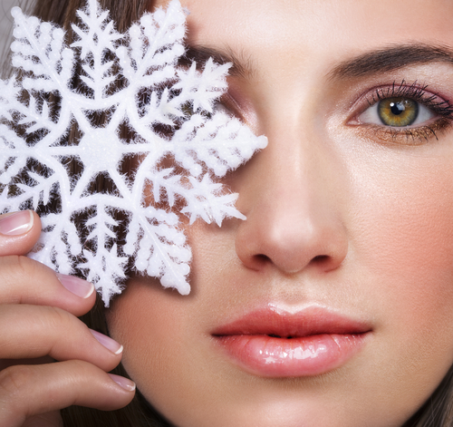 Close up of a beautiful woman with glowing skin holding a snowflake over one of her eyes
